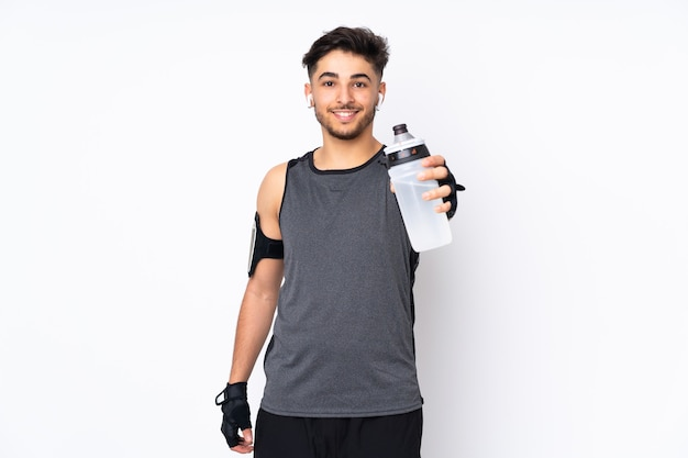 Homem árabe do esporte isolado na parede branca com garrafa de água esportiva