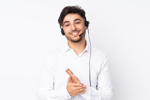 Homem árabe do telemarketing trabalhando com um fone de ouvido isolado no branco, aplaudindo