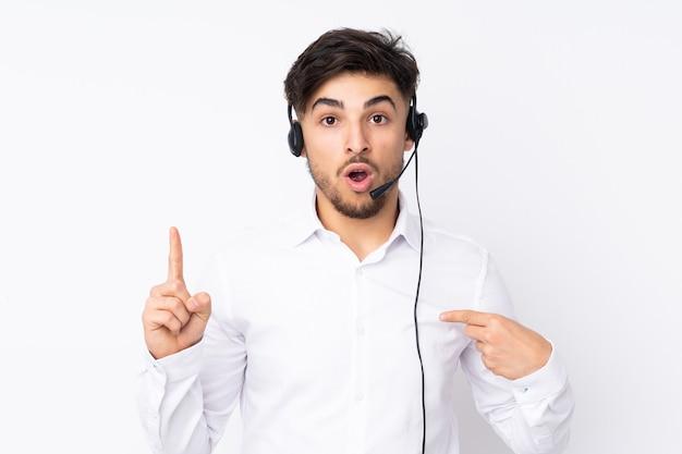 Homem árabe do telemarketing trabalhando com um fone de ouvido isolado no branco com expressão facial surpresa
