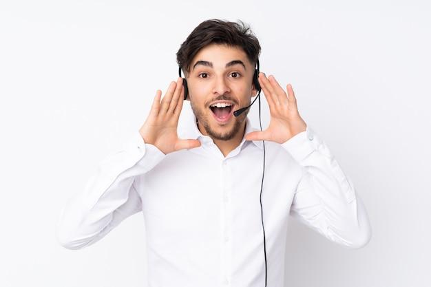 Homem árabe do telemarketing trabalhando com um fone de ouvido isolado no branco, gritando com a boca bem aberta