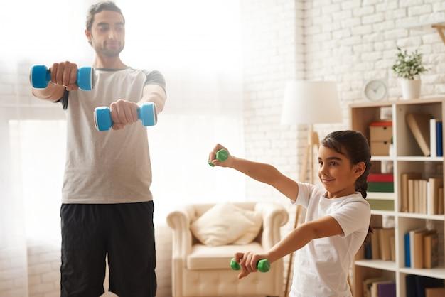 Homem árabe e garota fazendo exercícios com halteres