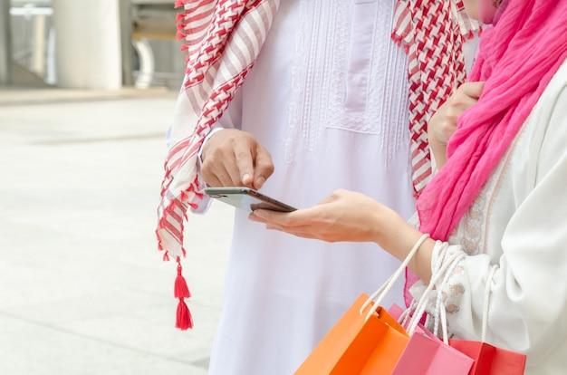 Homem árabe e mulher com sacos de compras com um telefone inteligente na cidade.