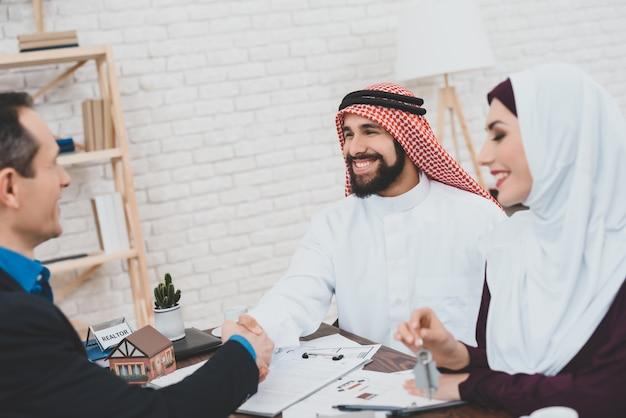 Homem árabe e mulher recebendo chaves da casa nova.