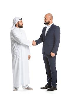 Homem árabe e seu parceiro de negócios apertando as mãos na superfície branca