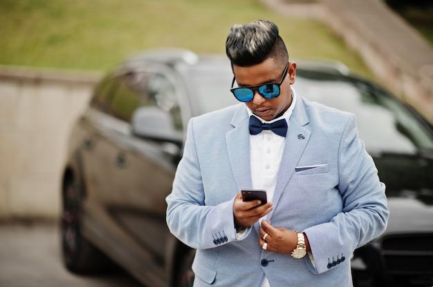 Homem árabe elegante casaco, gravata borboleta e óculos de sol contra carro preto suv. árabe rico com telefone celular.