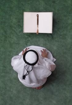 Homem árabe lê a vista superior do alcorão
