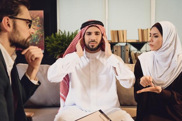 Homem árabe na recepção do terapeuta cutuca os ouvidos.