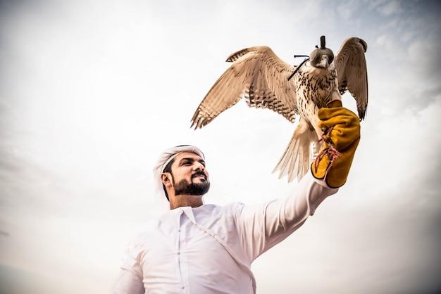 Homem árabe no deserto com seu falcão