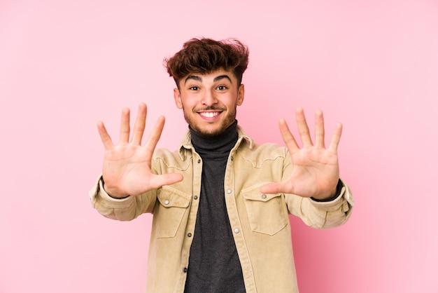 Homem árabe novo que levanta mostrando a tonelada do número com mãos.