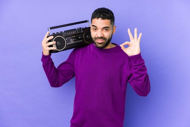 Homem árabe novo que mantém uma gaveta de rádio isolada música de escuta árabe nova alegre e segura mostrando o gesto aprovado.