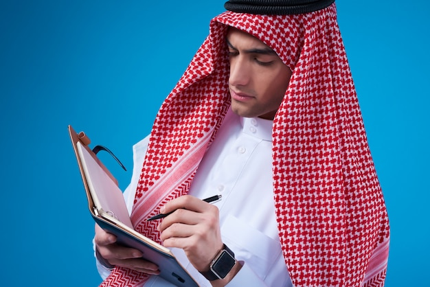 Homem árabe que toma notas no caderno isolado.
