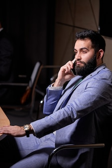 Homem árabe sentado, ouvindo o discurso de colegas, olhando para o lado, vestindo um elegante terno formal, discutindo sobre startups e finanças, em reunião de negócios inter-racial