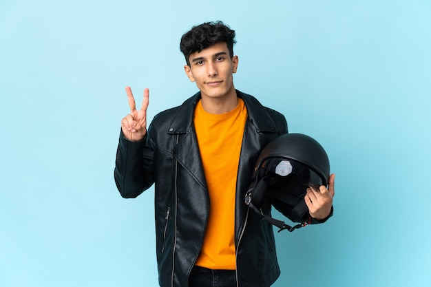 Homem argentino com capacete de motociclista sorrindo e mostrando sinal de vitória