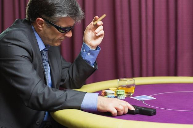 Homem, arma, sentando, pôquer, tabela