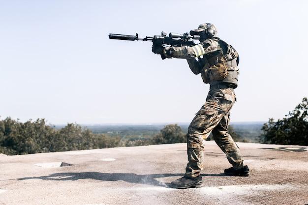 Homem armado camuflado com arma sniper na mão em pé no telhado