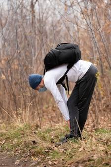 Homem armado com máscara facial e mochila na floresta