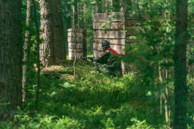 Homem armado em uma zona de conflito armado soldado em uniforme mirando com rifle de assalto ao ar livre, airsoft