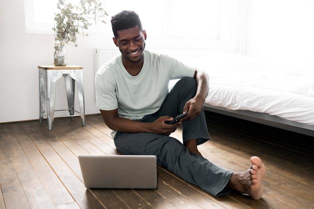 Homem armado no chão com laptop