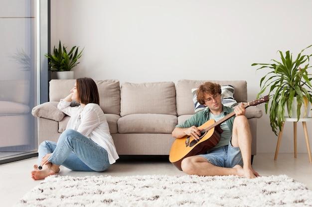 Homem armado tocando violão dentro de casa