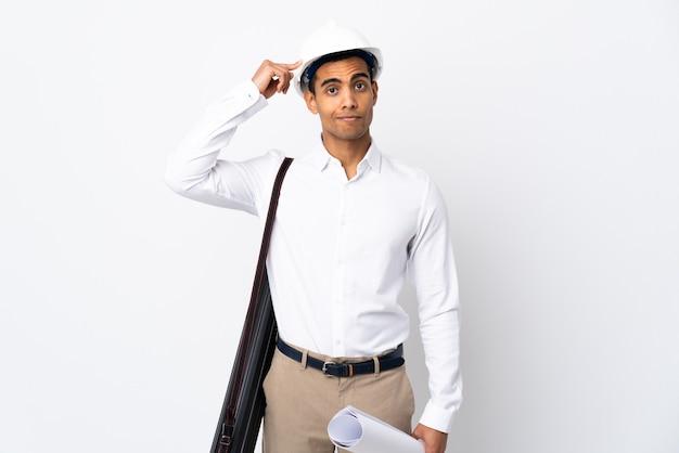 Homem arquiteto afro-americano com capacete e segurando plantas sobre fundo branco isolado _ tendo dúvidas e pensando