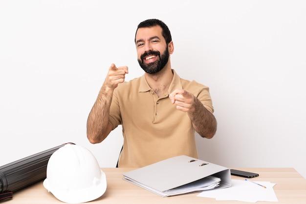 Homem arquiteto caucasiano com barba em uma mesa apontando para a frente com uma expressão feliz.
