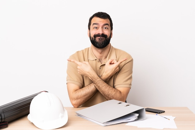 Homem arquiteto caucasiano com barba em uma mesa apontando para as laterais, tendo dúvidas.