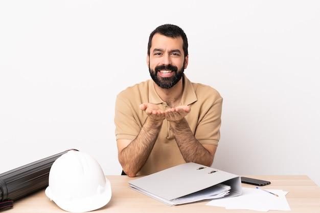Homem arquiteto caucasiano com barba em uma mesa segurando copyspace imaginário na palma da mão para inserir um anúncio.