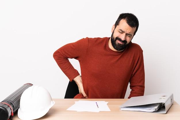 Homem arquiteto caucasiano com barba em uma mesa, sofrendo de dor nas costas por ter feito um esforço.