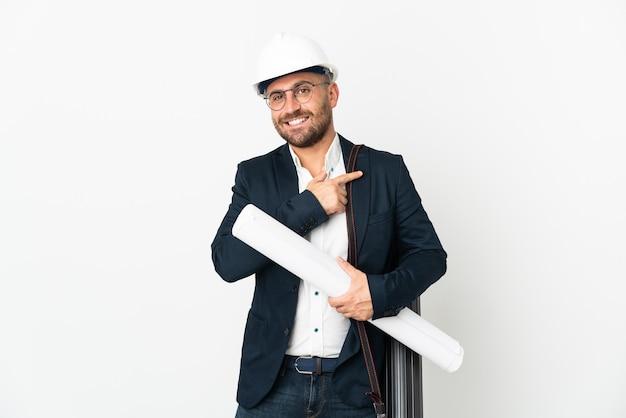 Homem arquiteto com capacete e segurando plantas isoladas no fundo branco apontando para o lado para apresentar um produto