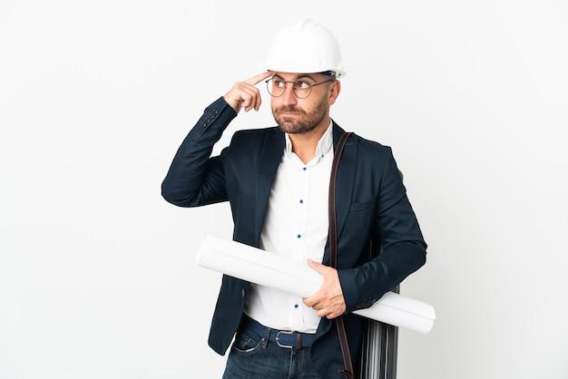 Homem arquiteto com capacete e segurando plantas isoladas no fundo branco, tendo dúvidas e pensando