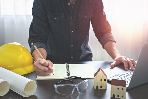 Homem arquiteto trabalhando com laptop, bloco de anotações e projetos