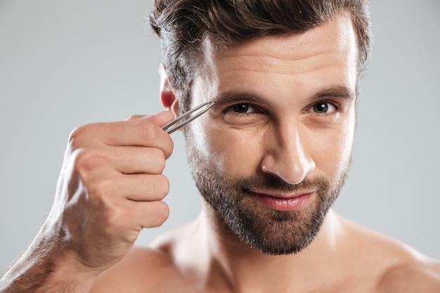 Homem arrancando as sobrancelhas isoladas