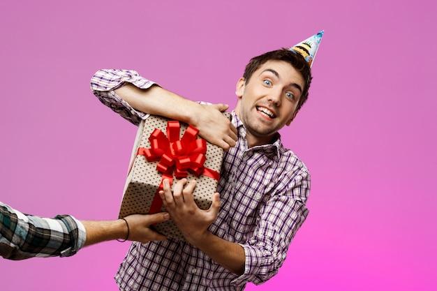 Homem arrancando o presente de aniversário em caixa sobre parede roxa.
