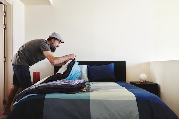 Homem arrumando o armário, colocando um monte de camisas na cama