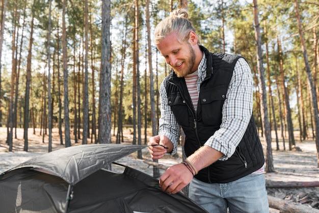 Homem arrumando sua barraca na natureza