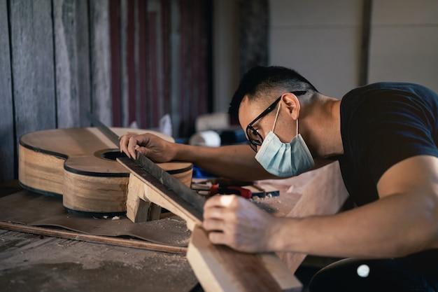 Homem artesanal fazendo violão na mesa de madeira, conceito de trabalho capenter