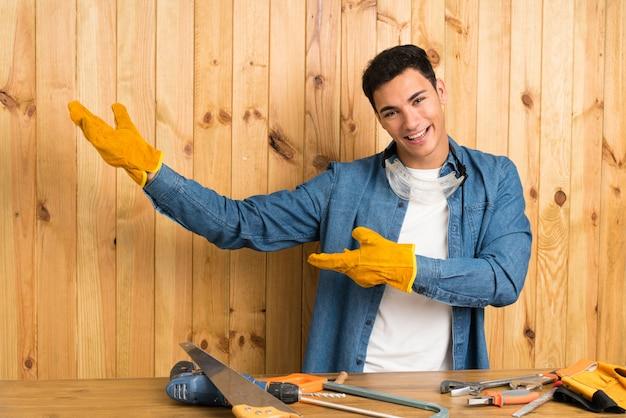 Homem artesão sobre parede de madeira, estendendo as mãos para o lado para convidar para vir