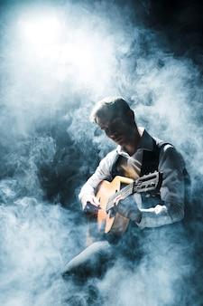 Homem artista no palco tocando violão e fumaça