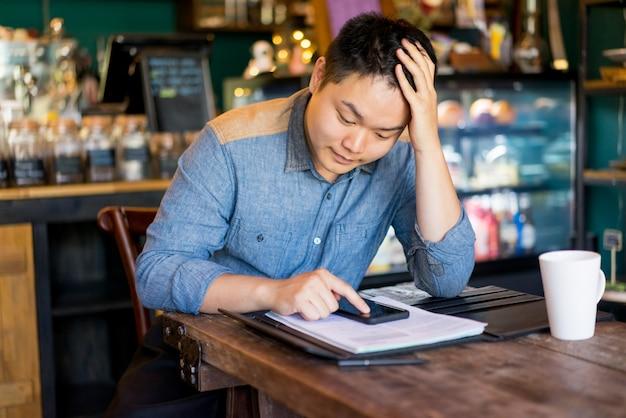 Homem asiático aborrecido que usa o dispositivo no café ao esperar o amigo.