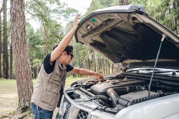 Homem asiático abrindo o capô de sua caminhonete para verificar as condições da falha do motor