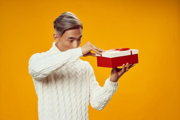 Homem asiático, abrindo um presente no dia do aniversário