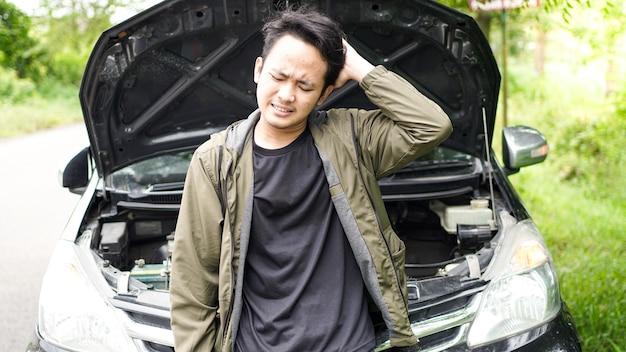 Homem asiático abriu o capô do carro enquanto estava confuso
