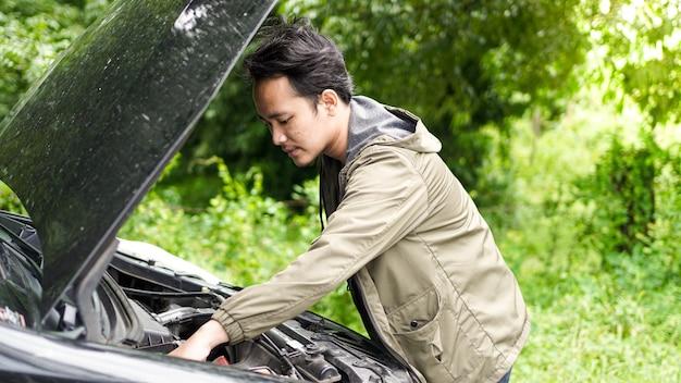 Homem asiático abriu o capô e verificou o carro