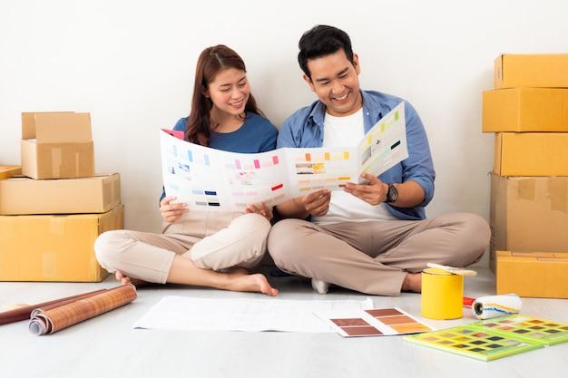 Homem asiático ad mulher design e pensando para decorar a casa