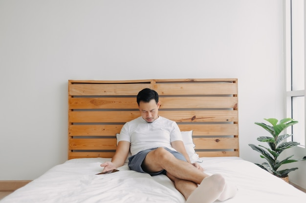 Homem asiático adormece na cama com o telefone na mão