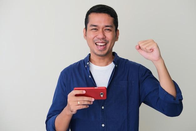 Homem asiático adulto cerrou os punhos mostrando gesto de vitória enquanto segurava o telefone celular
