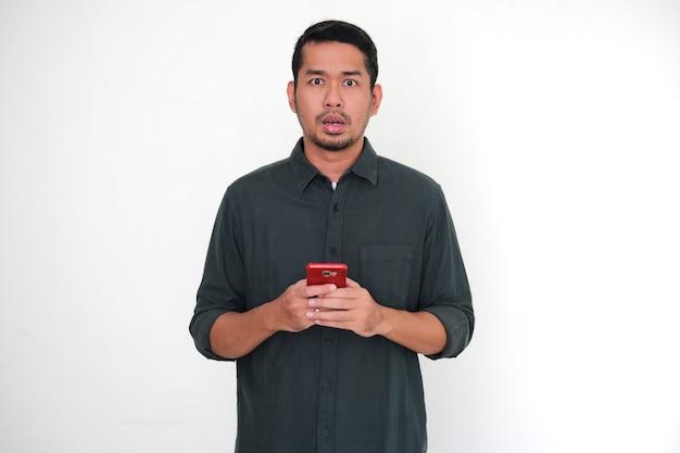 Homem asiático adulto mostrando expressão de choque ao segurar seu telefone celular