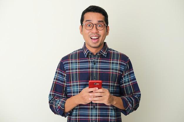 Homem asiático adulto mostrando expressão de surpresa ao segurar um telefone celular