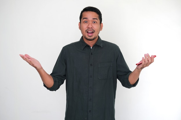 Homem asiático adulto mostrando um gesto duvidoso ao segurar seu telefone celular
