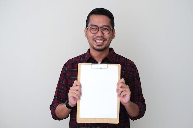 Homem asiático adulto mostrando um papel branco vazio em um bloco de notas com uma expressão de rosto sorridente